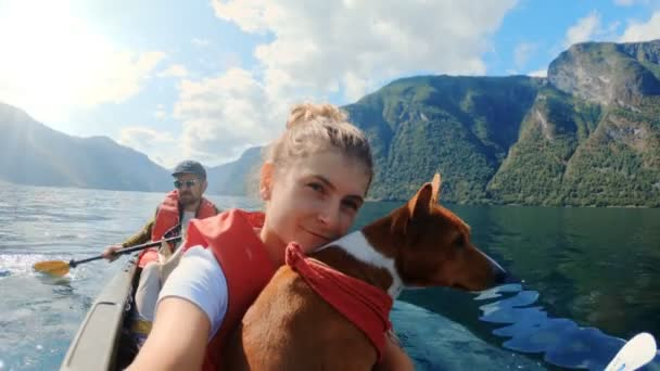 Happy girl traveller on kayak with cute dog