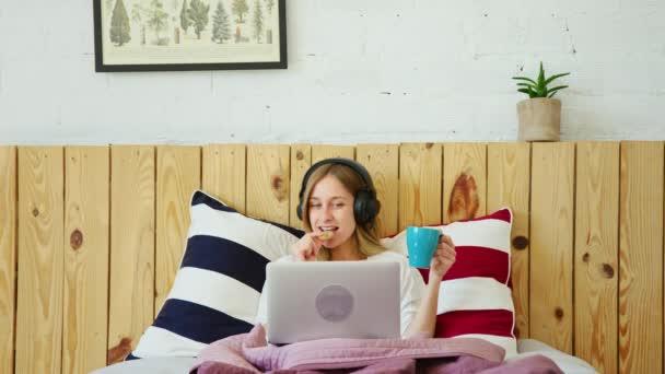 Mladá žena se sluchátky a notebookem v posteli