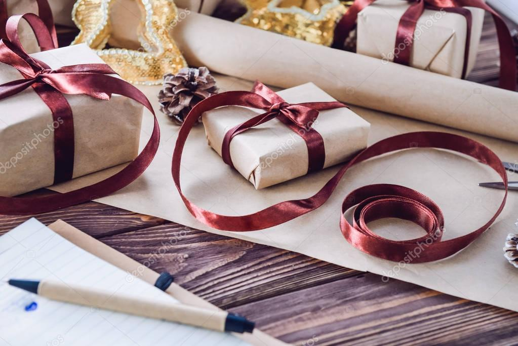 Holiday decorations and notebook with list of gifts on dark wooden rustic table. Christmas planning concept. Selective focus.