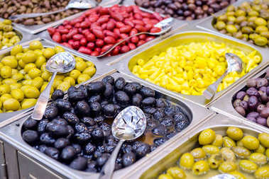 Bowls of various olives for sale at a market place. Organic, healthy, vegetarian diet food concept background. Selective focus