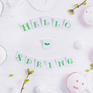 Top view composition of Hello spring lettering, branches with young shoots of greenery, easter cupcakes, merengue sweets, handcraft bird figure on wooden background. Art concept. Selective focus.