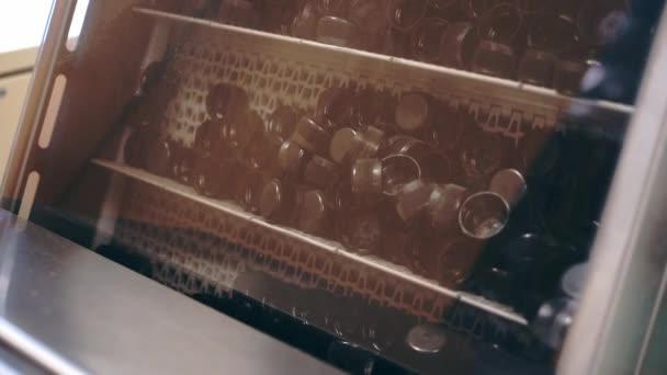 Workshop výroba plastového víčka na lahve. Různé plastové krytky v černém. Zařízení v podniku. Obal na láhev