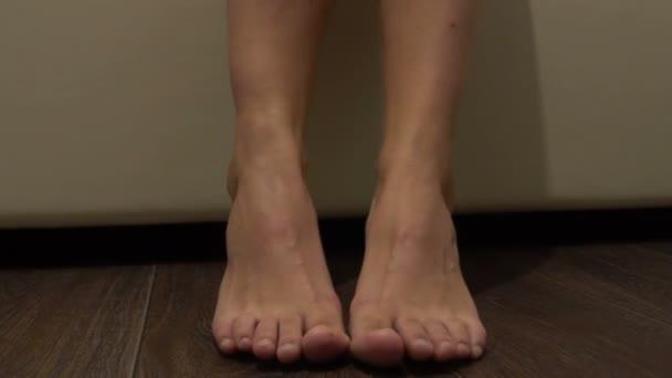 Ženské nohy naboso u postele