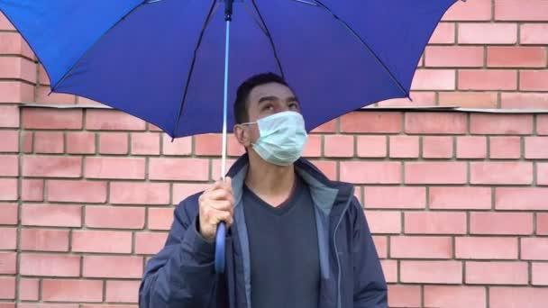 Sad man in mask standing alone under the umbrella, social distance, self isolation, quarantine