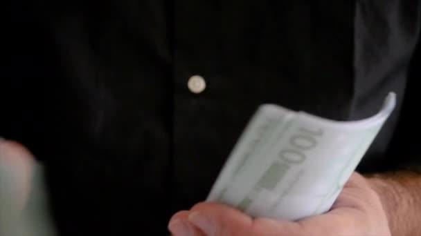 Uomo che raccoglie delle banconote da 100 euro. Homályos