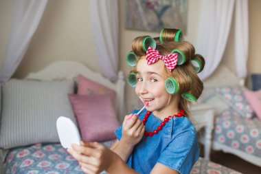Portrait of funny little girl with a curlers paints lips
