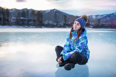 Young pretty girl sits on an ice in winter, Altai, Russia