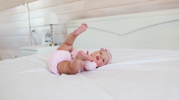 hübsches Kind in rosa Kleid liegt auf dem Rücken auf einem Bett zu Hause