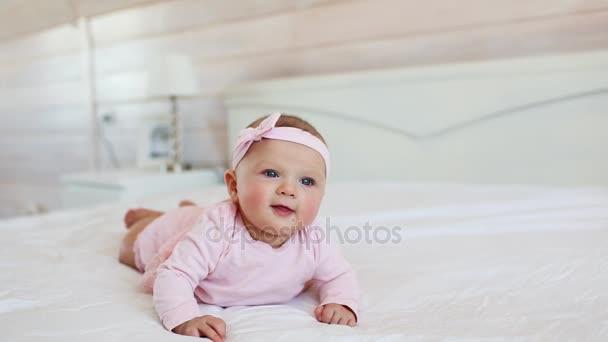 Portrét v růžových šatech na posteli doma docela kojenecká