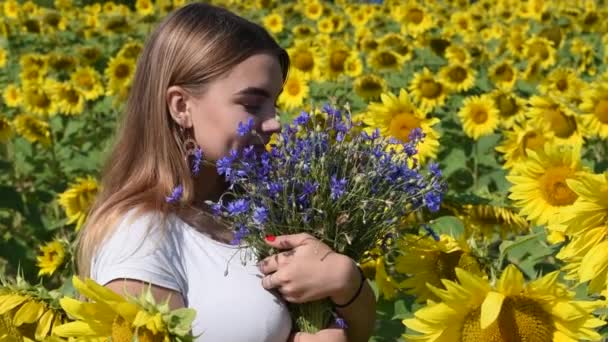 Beautiful young girl in the middle of a field of blooming sunflowers with a bouquet of blue wildflowers.