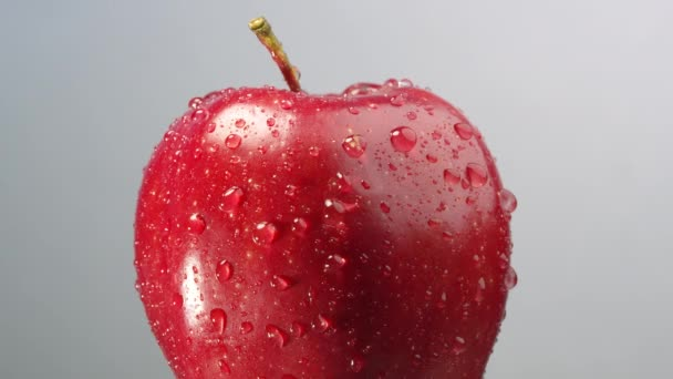 Red apple with water droplets on it slowly rotating looking refreshing to eat.