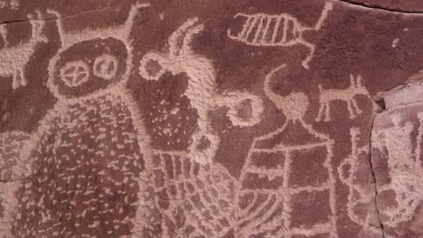 Közelről látjuk a kőfalba vésett petroglifeket, melyeket őslakos amerikaiakból faragtak Utah-ban, a Kilenc Mérföld kanyonban..