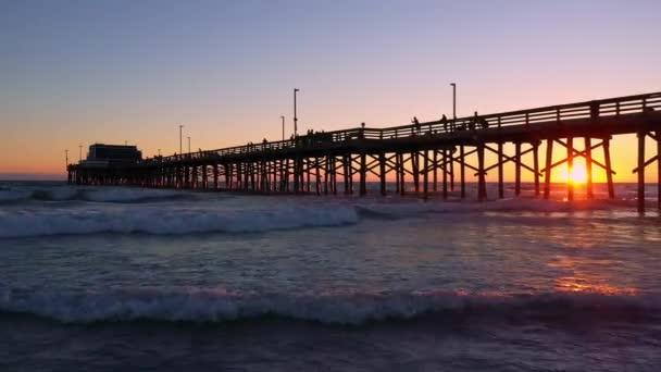 Vlny valící se po pláži při západu slunce na Newport Beach při pohledu na molo.