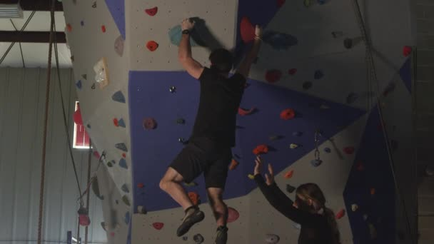 Couple in gym working out on rock climbing wall while he climbs and she celebrates with him as he drops.