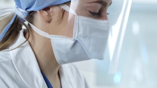 Női nővér dolgozik a laborban nézett fel arc maszk és pajzs eltakarja az arcát.