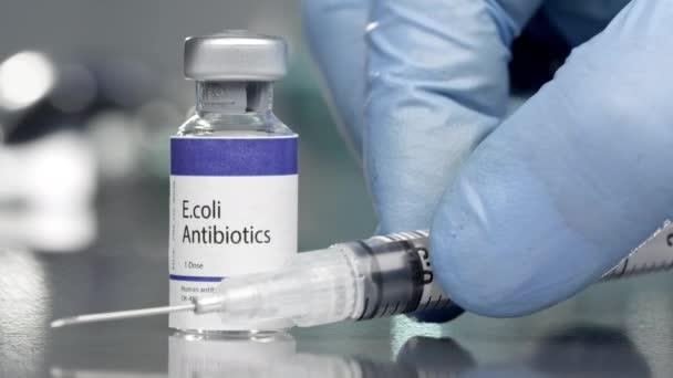 E.coli Antibiotika Fläschchen im Mediallabor mit Spritze daneben.