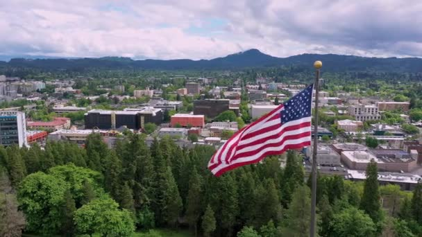American Flag waving in aerial view of Eugene Oregon slowly flying around the flag.