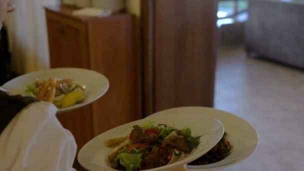Číšník v restauraci přináší lahodné čerstvé jídlo na stůl.