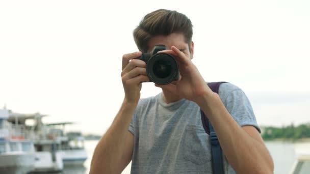 Portrait of professional photographer using his photo camera.