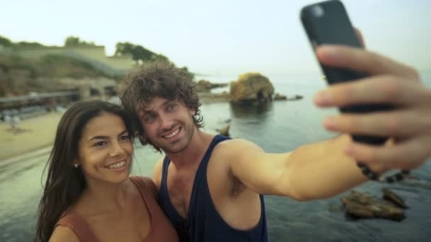 Beautiful young couple taking selfies on the beach.