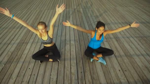 Dvě mladé dámy sedící v lotus představují a meditovat u moře