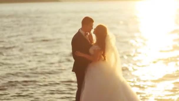 Mladý ženich nosí elegantní oblek a krásná nevěsta v bílé luxusní svatební šaty líbání u řeky