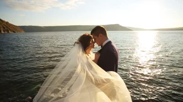 Stylový šťastný ženich nošení na rukou jeho krásná mladá nevěsta ve světle slunce a s úsměvem, při pobytu na vrcholu hory.