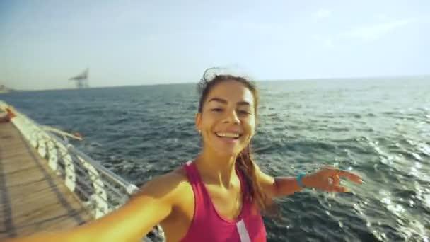 Roztomilá mladá brunetka pořízení selfie a položenou na dřevěném chodníku po ranní jogging.