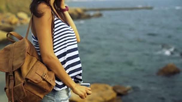 schöne sexy Frau trägt lässige Kleidung, Hut und Sonnenbrille und macht schöne Fotos von der blauen Tiefsee.