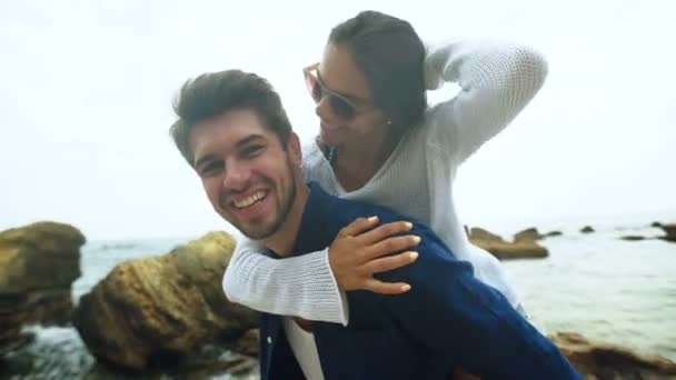 Attractive tanned woman in a white sweater and his happy boyfriend posing on a camera .
