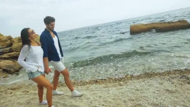 Glückliches junges Paar tragen dasselbe Paar Schuhe, zu Fuß am Strand