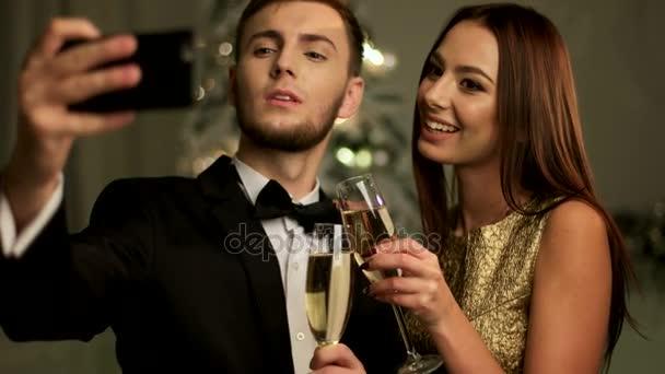 glückliches Paar macht Selfies am Neujahrstag, hält zwei Gläser Champagner in den Händen.