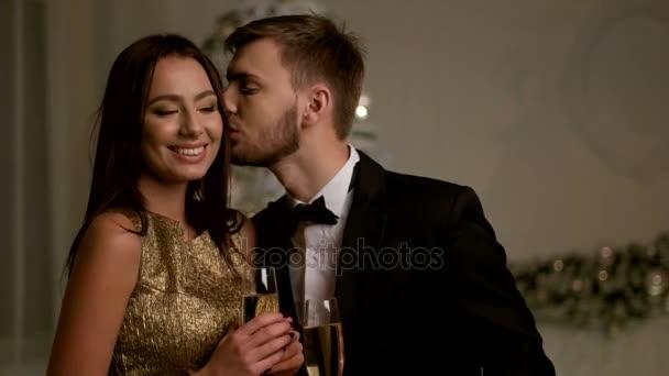 glückliche junge Familie hält zwei Gläser Champagner in der Hand und feiert gemeinsam das neue Jahr.