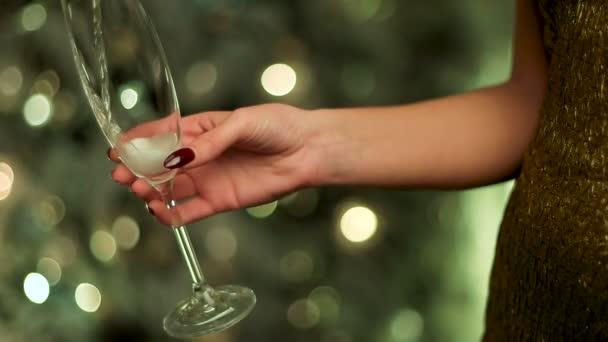 Žena ve zlatých šatech drží sklenku šampaňského jiskru na nový rok.
