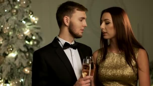 Mladá rodina si přejí všechno nejlepší s dvě sklenice šampaňského na nový rok večer
