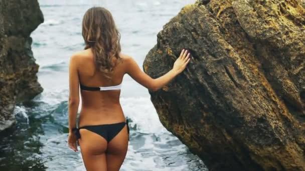 Krásná dáma nosí černé a bílé bikiny chůzi po vodě na pláži