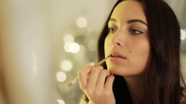 Close up of attractive young serious lady with brown hair doing natural make-up at home.