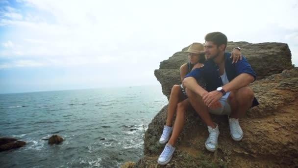 Mladý šťastný pár sedí na kameni v stejné bílé boty a užívat si hezký den na pláži