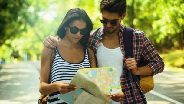 Dva mladí lidé, relaxaci na zelený park a dělat nový plán pro svou cestu.