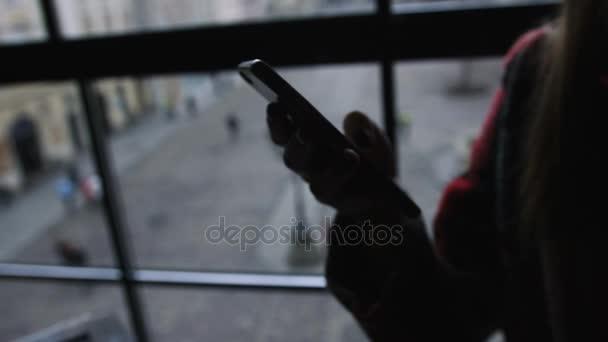 Silhouette der Frau Nutzung Handy in Stadt-Café am Sonnenuntergang Architektur und Straße der Hintergrund jedoch unscharf. 4k