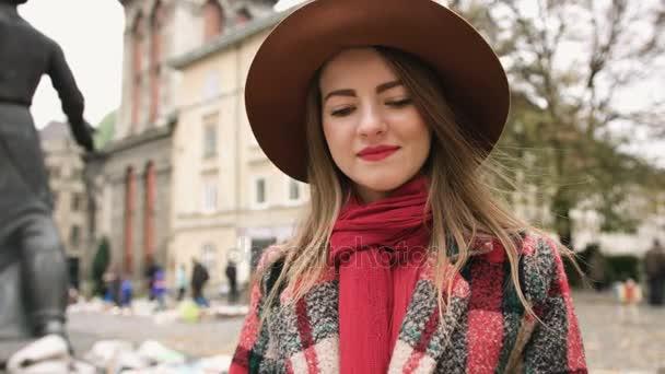 Fiatal gyönyörű lány kalap olvasókönyv a Városligetben. Lassú mozgás.