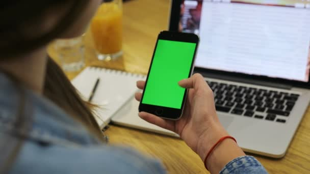 Žena používající vertikální smartphone s zeleným plátnem. Close-up shot Zenske rukou rolování mobilní telefon. Chroma klíč.