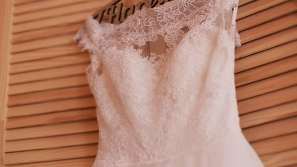 Beautiful luxurious wedding dress on hanger on wooden background. Wedding preparation