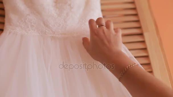 Zblízka Zenske ruky na bílé svatební šaty. Před svatební obřad. Nevěsta
