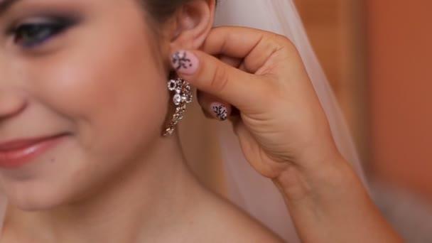 Družička pomáhá nevěstě se oblékat se před svatební obřad. pomáhá na náušnice. Detailní záběr