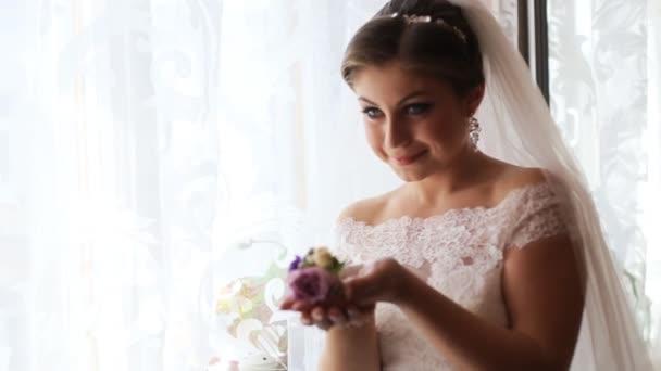 Krásná nevěsta v luxusních svatebních šatech u okna před svatební obřad. Žena hospodářství květiny