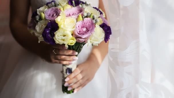 Beautiful wedding flower bouquet in brides hands. Close up. Yellow, pink and purple bridal bouquet. Bride holding wedding bouquet