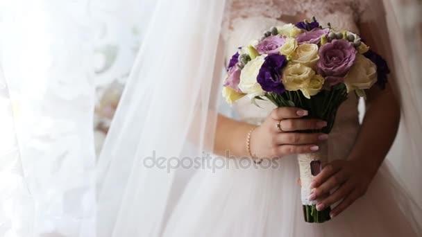 Držení svatební kytice nevěsty. Krásné svatební kytice v rukou nevěsty. Zblízka. Žluté, růžové a fialové svatební kytice