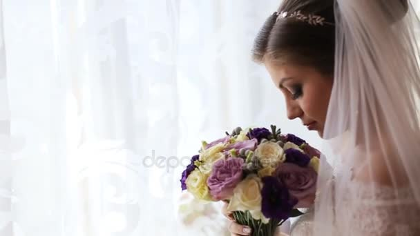 Beautiful bride in luxury wedding dress smelling flower bouquet. Close up