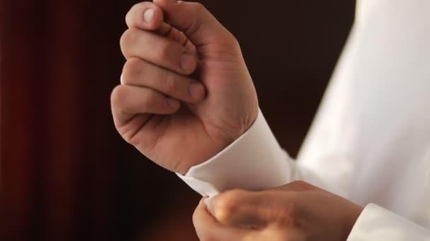 Ženicha zapínání manžety na bílé tričko s rukávem. Detailní záběr záběr